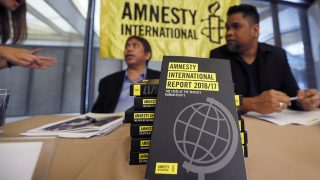 """A reporter, left, talks to Amnesty International, Philippines' Jose Noel Olano and Wilnor Papa, right, following the release of the 2016/17 Amnesty International report which they released at a news conference Wednesday, Feb. 22, 2017, in suburban Quezon city northeast of Manila, Philippines. Amnesty International says """"toxic"""" fear-mongering by anti-establishment politicians, among them President Donald Trump and the leaders of Turkey, Hungary and the Philippines, is contributing to a global pushback against human rights. (AP Photo/Bullit Marquez)"""